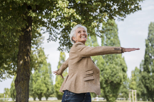 Happy senior woman with outstretched arms in a park - DIGF05113