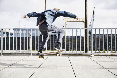 Rear view of teenage boy doing skateboard trick on walkway - TGBF00027