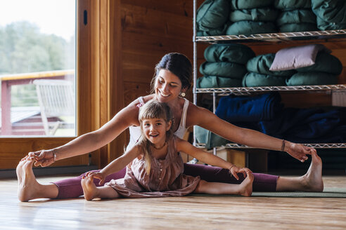 Mother and daughter practicing yoga while sitting with legs apart on floor - TGBF00057