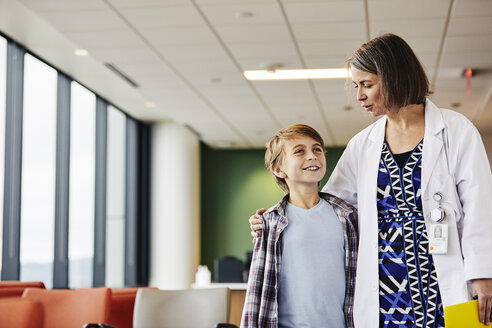 Smiling mature female pediatrician talking while walking with boy in corridor at hospital - TGBF00222