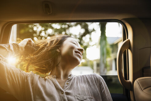 Happy young woman hanging head outside of car window - TGBF00243