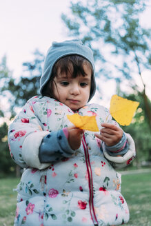 Portrait of fashionable little girl with yellow autumn leaves - GEMF02408