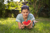 Portrait of girl lying on meadow in the garden eating watermelon - LVF07411