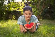 Portrait of girl lying on meadow in the garden eating watermelon - LVF07411