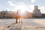 Italy, Molise, Termoli, young couple in the beach at sunrise - FLMF00019