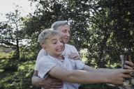 Grandmother and playful grandson taking a selfie in garden - KMKF00530