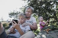 Grandmother with grandchildren in garden - KMKF00533