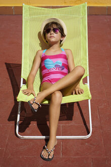 Young girl sitting in sun lounger, sunbathing - JSMF00441