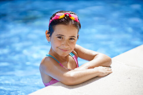 Young girl wearing swimmming goggles, at swimming pool - JSMF00444