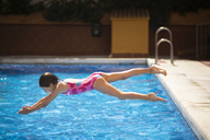 Young girl jumping head first into the pool in summer - JSMF00447