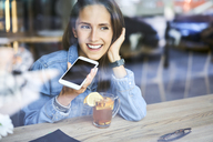 Smiling young woman speaking on phone in cafe while having tea - BSZF00567