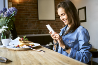 Smiling young woman with plate of pancakes using phone in cafe - BSZF00576