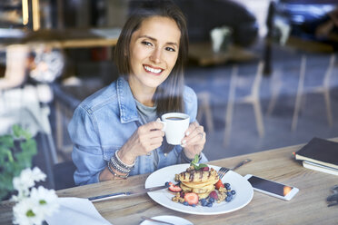 Portrait of smiling young woman enjoying pancakes and coffee in cafe - BSZF00579
