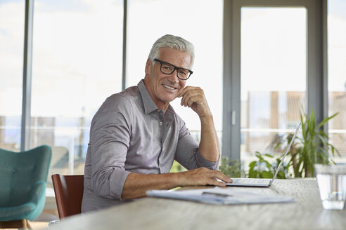 Portrait of smiling mature man using laptop on table at home - RBF06498