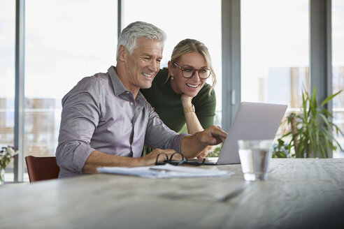 Smiling mature couple using laptop on table at home - RBF06501