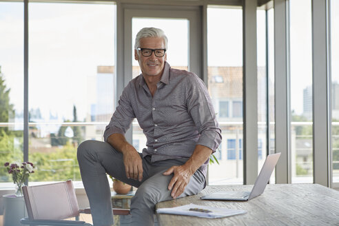 Portrait of smiling mature man with laptop sitting on table at home - RBF06504