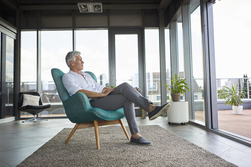 Pensive mature man sitting in armchair at the window at home - RBF06510