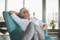Mature man relaxing in armchair at the window at home - RBF06516