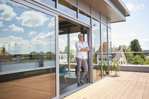 Mature man relaxing standing at roof terrace at home - RBF06525