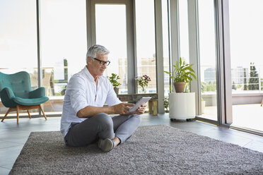Mature man sitting on carpet at home using tablet - RBF06528