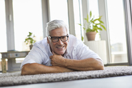 Smiling mature man relaxing lying on carpet at home - RBF06531