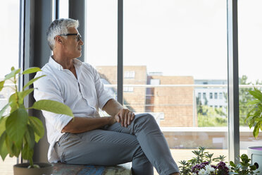Pensive mature man sitting at the window at home - RBF06534
