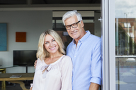 Portrait of smiling mature couple at the balcony at home - RBF06537