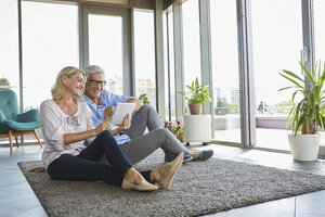 Smiling mature couple relaxing at home sitting on carpet sharing tablet - RBF06552
