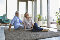 Portrait of smiling mature couple relaxing at home sitting on carpet - RBF06558