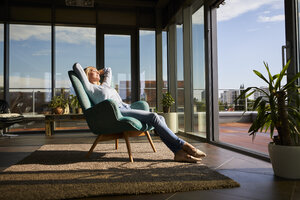 Mature woman relaxing in armchair in sunlight at home - RBF06564