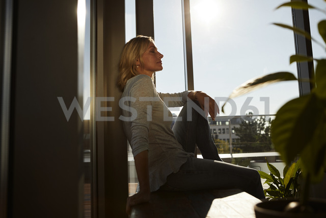 Relaxed mature woman sitting in sunlight at home - RBF06573 - Rainer Berg/Westend61