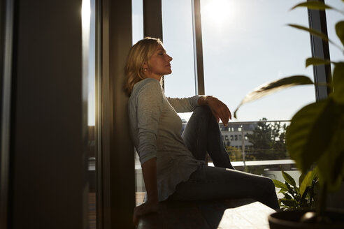 Relaxed mature woman sitting in sunlight at home - RBF06573