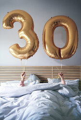 Woman with golden balloons celebrating her birthday in bed - ABIF00963