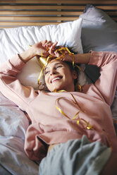 Woman resting after birthday party on bed - ABIF00972