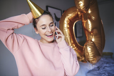 Woman with party hat using mobile phone - ABIF00981