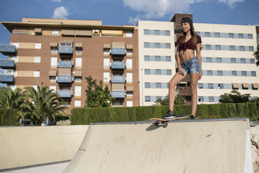 Young pretty woman standing on skate ramp - JASF01942