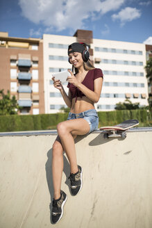 Young pretty woman sitting on wall of skatepark, listen music, using digital tablet - JASF01945