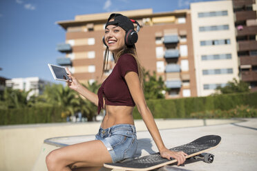 Young pretty woman sitting on wall of skatepark, listen music, using digital tablet - JASF01948