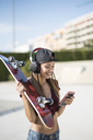 Young pretty woman in skatepark, listen music, using smartphone - JASF01951
