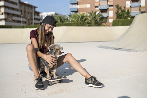 Young woman sitting on skateboard, stroking her dog - JASF01954