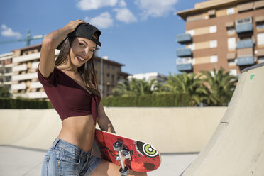 Young woman in skate park, carrying skateboard - JASF01957