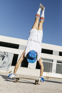 Back view of man in stylish sportive outfit standing on skateboard upside down against blue sky - JRFF01844