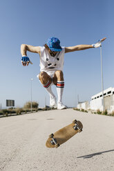 Sportive man jumping above ground with skateboard performing trick - JRFF01847