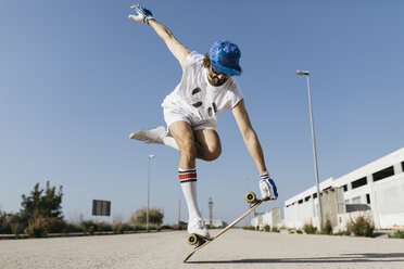 Man in stylish sportive outfit standing on skateboard against blue sky - JRFF01850