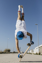 Back view of man in stylish sportive outfit standing on skateboard upside down against blue sky - JRFF01853