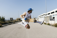 Sportive man jumping above ground with skateboard on hands - JRFF01859