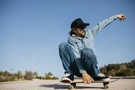 Trendy man in denim and cap skateboarding - JRFF01862