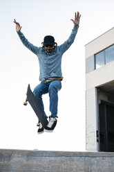 Trendy man in denim and cap skateboarding, doing jump with skateboard from concrete ramp - JRFF01865