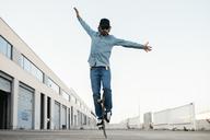 Trendy man in denim and cap skateboarding, standing on skateboard - JRFF01868