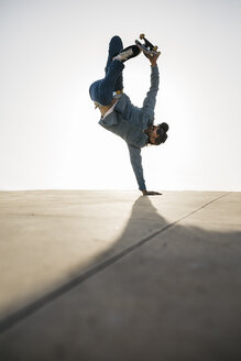 Stylish man in denim outfit showing trick with skate in handstand - JRFF01871
